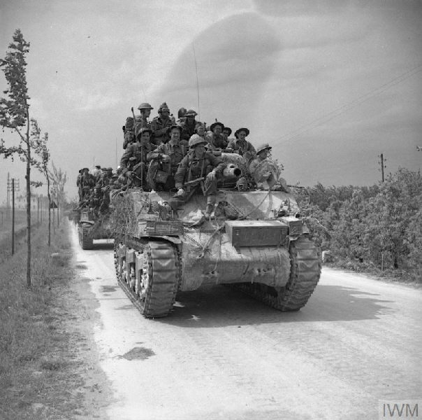 Men of the 2nd Lancashire Fusiliers are carried forward on Sherman tanks near Ferrara, 22 April 1945.